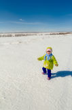The joyful child walks on a snow-covered field. Royalty Free Stock Photos