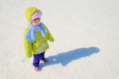 The joyful child walks on a snow-covered field. Royalty Free Stock Photography