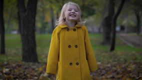 Joyful childhood, portrait of a cute girl have fun in autumn park while relaxing outdoors