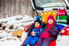 Joyful children enjoy many Christmas presents in car trunk. Cold winter, snow weather royalty free stock photo