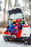 Joyful children enjoy many Christmas presents in car trunk. Cold winter, snow weather stock photos
