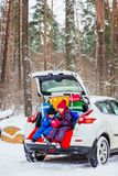 Joyful children enjoy many Christmas presents in car trunk. Cold winter, snow weather royalty free stock images