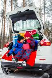 Joyful children enjoy many Christmas presents in car trunk. Cold winter, snow weather royalty free stock photography
