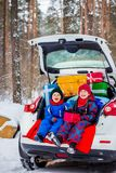 Joyful children enjoy many Christmas presents in car trunk. Cold winter, snow weather royalty free stock image
