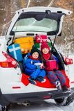 Joyful children enjoy many Christmas presents in car trunk. Cold winter, snow weather stock image