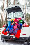 Joyful children enjoy many Christmas presents in car trunk. Cold winter, snow weather stock photo