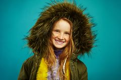 Joyful children girl in demi season winter jacket isolated on blue background. Smiling teenage child expresses sincere royalty free stock image