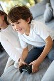 Joyful children at home playing video games Stock Photo