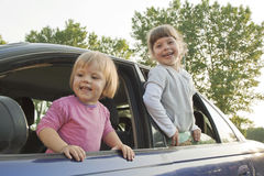 Joyful children look out of the car Stock Image