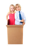 Joyful children look out from a cardboard box stock photography