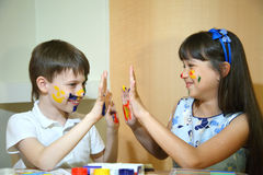 Joyful children with paints on their faces. Children paints faces with colors. Royalty Free Stock Photos
