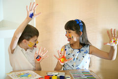 Joyful children with paints on their faces. Children paints faces with colors. Stock Photo