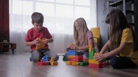Joyful children play educational games, build toys from colored blocks of designer