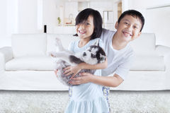 Joyful children play with husky puppy at home Royalty Free Stock Photography