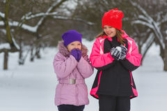 Joyful children playing in snow. Two happy girls having fun outside winter day Stock Photo