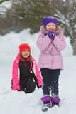 Joyful children playing in snow. Two happy girls having fun outside winter day.  Stock Photography