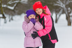 Joyful children playing in snow. Two happy girls having fun outside winter day.  Stock Photos