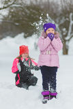 Joyful children playing in snow. Two happy girls having fun outside winter day.  royalty free stock image
