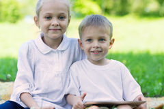 Joyful children use a tablet pc Royalty Free Stock Photo