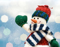 Joyful Christmas snowman on winter landscape with blurred lights background Stock Photos