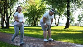 Joyful chubby girl outrunning obese man tired after jogging, exhausting workouts stock images