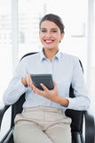 Joyful classy brown haired businesswoman using a calculator. In bright office Royalty Free Stock Photos