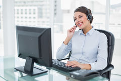 Joyful classy brown haired operator answering a call. In bright office Royalty Free Stock Photo