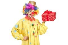 Joyful clown with a present Stock Photos
