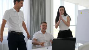 Joyful collaborators With computer on table applaud at work in office space. Joyful collaborators With computer on table applaud and Shake arms at work in office stock footage