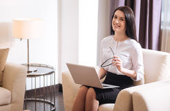 Joyful confident businesswoman sitting in the armchair. Comfortable workplace. Joyful nice confident businesswoman sitting in the armchair and working on her Royalty Free Stock Photos