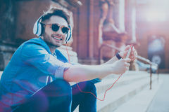 Joyful content man sitting on the fotsteps. Enjoy sunny weather. Cheeful glad young man smiling and listenig to music while resting on the footsteps Royalty Free Stock Photo
