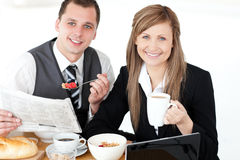 Joyful couple of businesspeople having breakfast. Smiling at the camera against white background Stock Photography