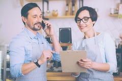 Joyful couple of cafe owners talkign on smart phone Royalty Free Stock Images