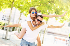 Joyful couple doing piggyback in the park Royalty Free Stock Photo