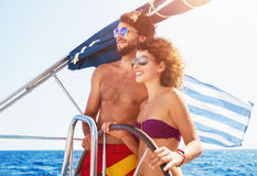 Joyful couple driving sailboat Stock Photos
