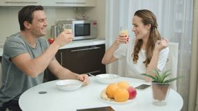 Happy couple having fun at kitchen. Smiling man and woman clinking glasses stock footage