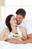 Joyful couple eating pancakes lying on their bed Royalty Free Stock Photography