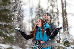 Joyful couple enjoying the snowfall Royalty Free Stock Image