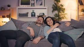 Joyful couple watching TV at night laughing having fun talking at home stock video footage