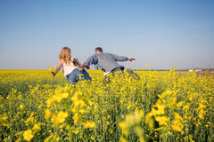 Joyful couple is having fun in a field of yellow flowers Stock Photo
