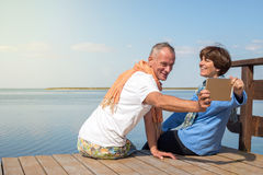 Joyful couple having fun, taking selfie. Using tablet pc on the sea coast. Happy people on the vacation Royalty Free Stock Photography