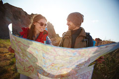 Joyful Couple Hiking in Mountains. Joyful travelers, young men and woman, taking a hike through mountains in bright sunlight, stopping to look at huge map with Stock Image