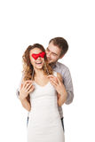 Joyful couple holding hearts by eyes and laughing Stock Images