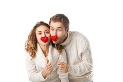 Joyful couple holding red hearts and laughing Stock Photo