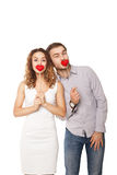 Joyful couple holding red hearts and laughing Royalty Free Stock Photography