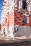 Joyful couple jumping on corner of building in city Royalty Free Stock Images