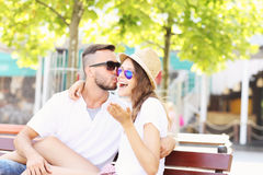 Joyful couple kissing on a bench Royalty Free Stock Photography