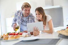 Joyful couple in kitchen seeking for a recipe Stock Images
