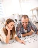 Joyful couple looking at construction plan Stock Photos