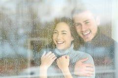 Joyful couple looking through a window a rainy day Stock Photo